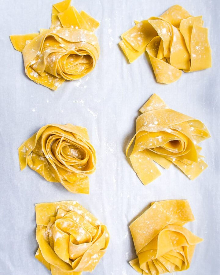 six nests of fresh pasta dough on parchment paper