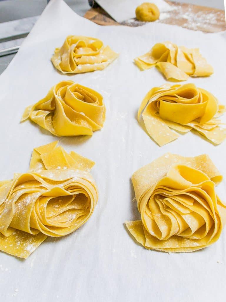 fresh pasta dough nests on parchment paper