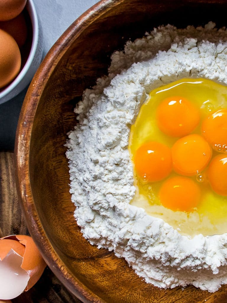 cracked eggs and flour in wooden bowl fresh pasta recipe