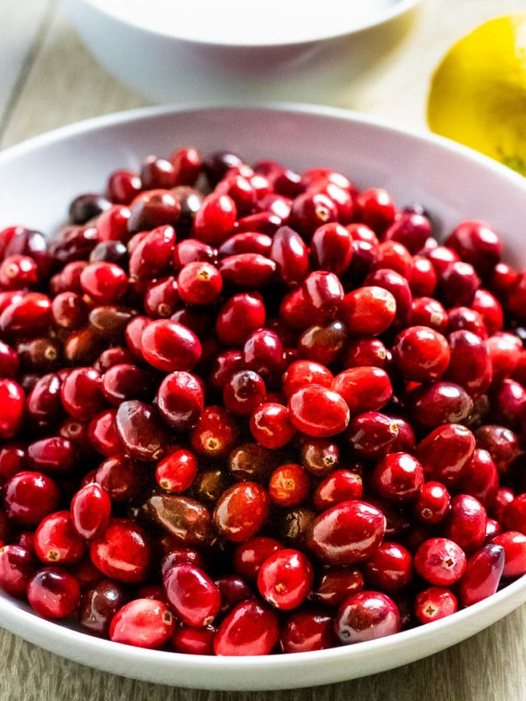 red cranberries in a bowl next to lemon and white bowl