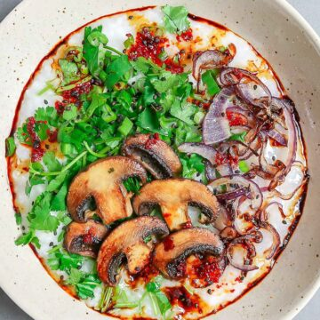 mushroom rice porridge with green herbs in a bowl