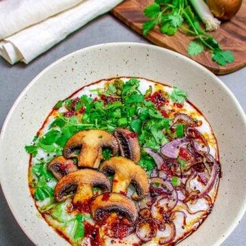 mushroom rice porridge in a bowl with green herbs
