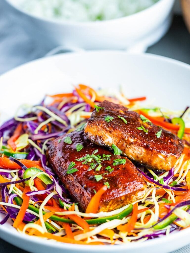 oven baked salmon with spice rub on rainbow slaw salad in white bowl