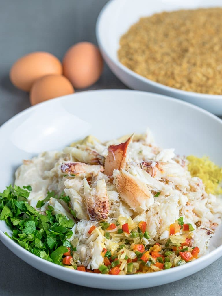 crab cake ingredients in a bowl with three eggs