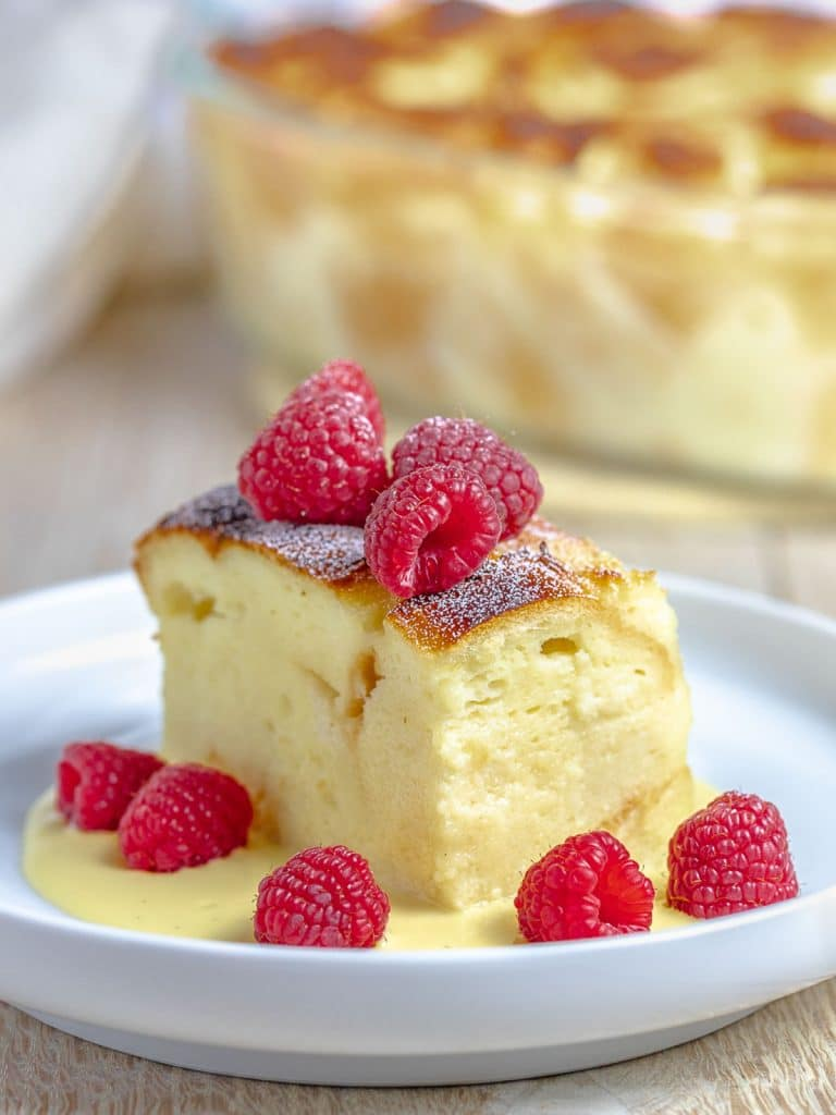 custard bread pudding with vanilla sauce and red raspberries