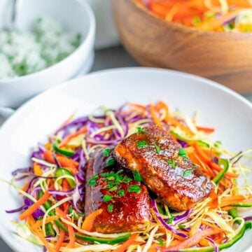 oven baked salmon with spice rub on rainbow salad in white bowl