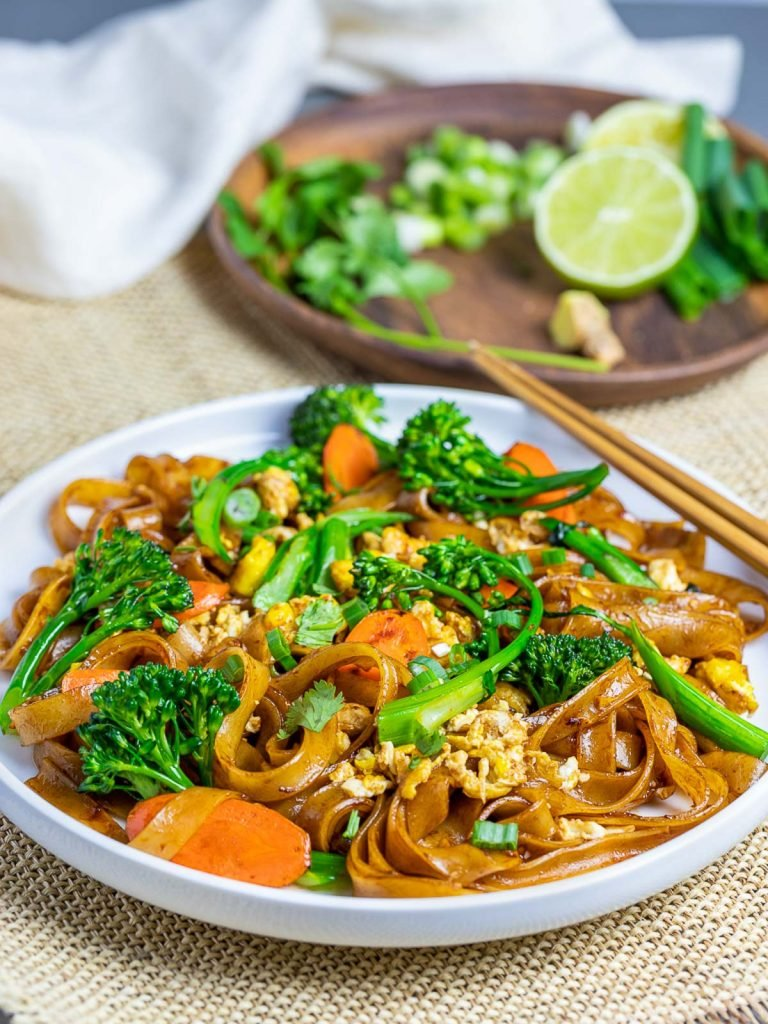 pad see ew thai noodles on white bowl with chopsticks and vegetables