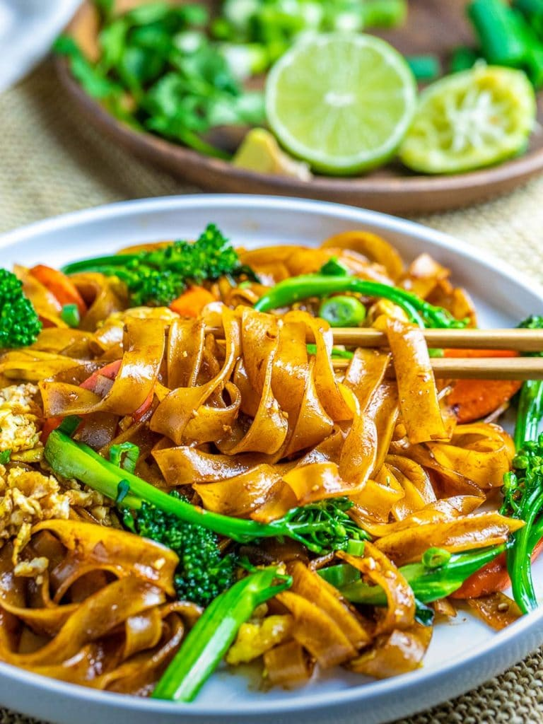 pad see ew thai noodles on white plate with vegetables and lime