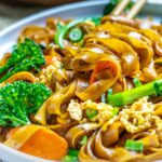 pad see ew thai noodles with vegetables on white plate