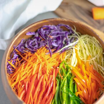 rainbow cabbage salad in wooden bowl next to cutting board