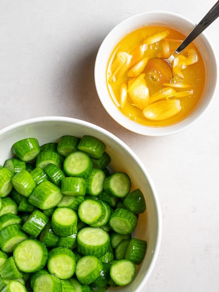 chopped green persian cucumbers in a bowl next to a garlic chili oil dressing