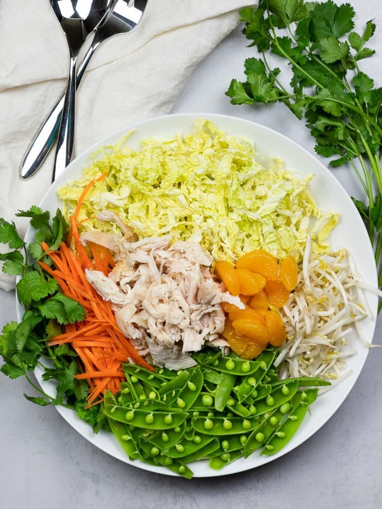 healthy Chinese chicken salad in a white plate with cilantro and silverware
