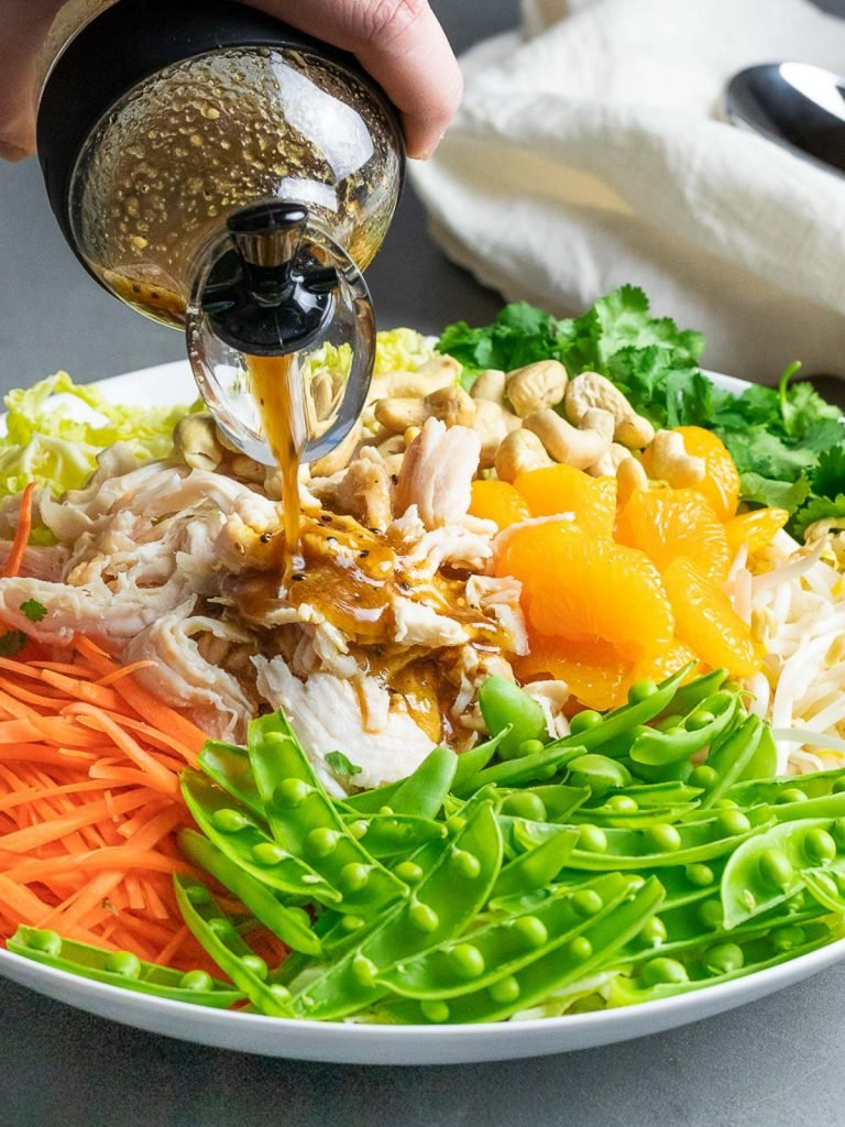 healthy chinese chicken salad with peas, mandarin oranges, carrots, and dressing