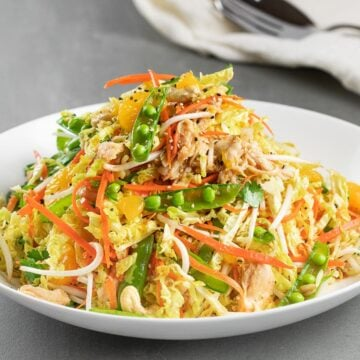 healthy Chinese chicken salad in a white bowl and grey tile