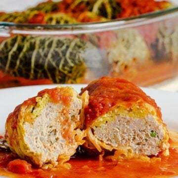 inside of easy stuffed cabbage rolls with meat filling on a white plate covered in a red tomato sauce