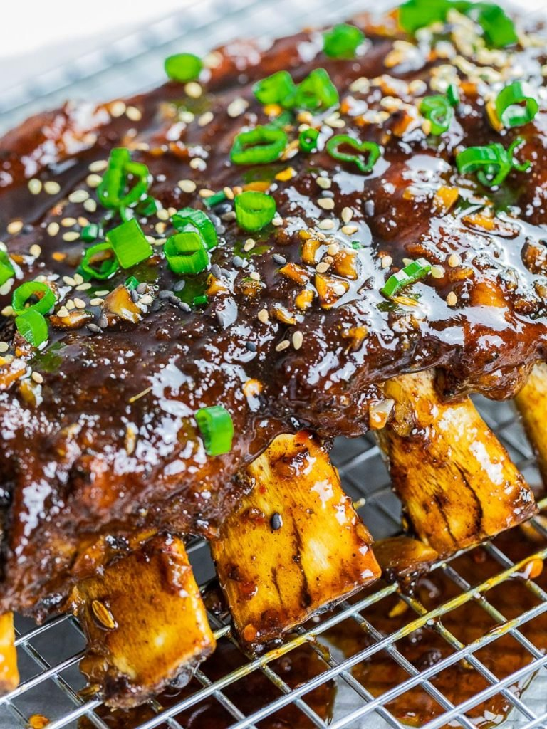 Instant Pot Asian ribs on a cooling rack garnished with scallions and sesame seeds