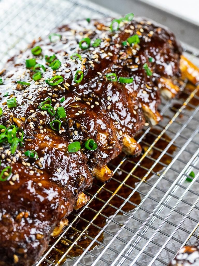 Instant Pot Asian ribs on a cooling rack with scallions