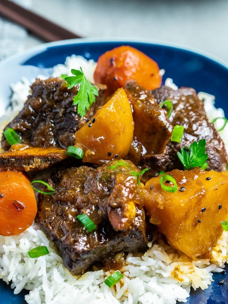 Korean style short ribs with potatoes and carrots with rice on blue plate