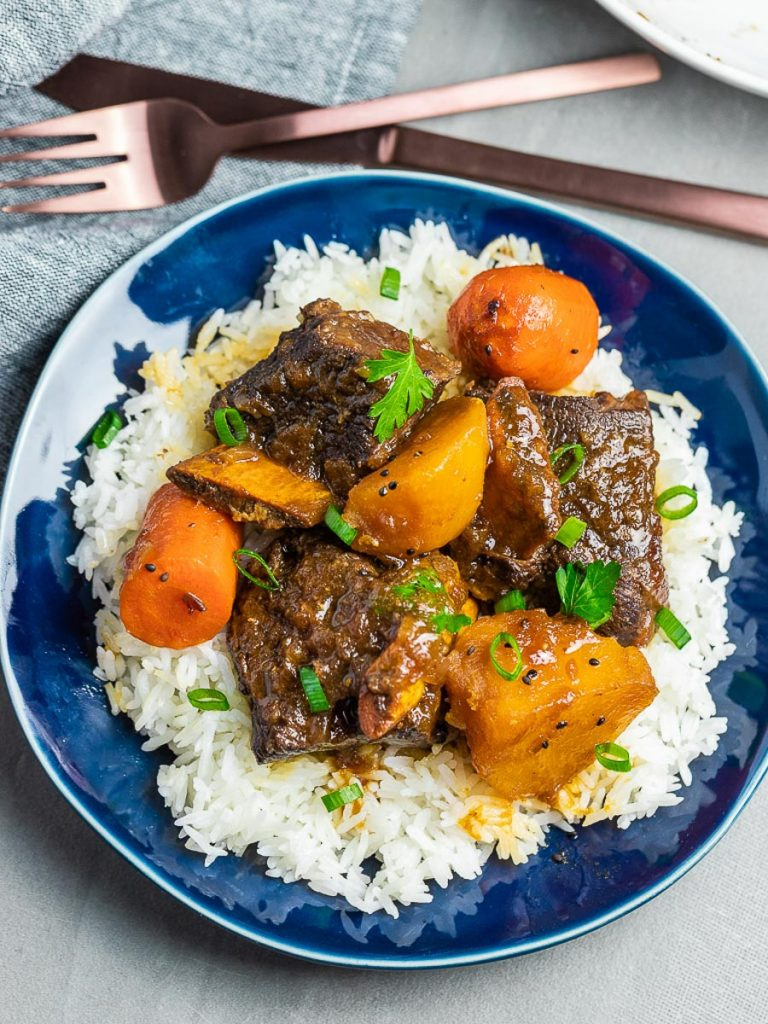 Korean style short ribs with potatoes and carrots with rice on a blue plate next to fork and knife
