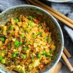 ketchup fried rice with peas and vegetables in two bowls with chopsticks