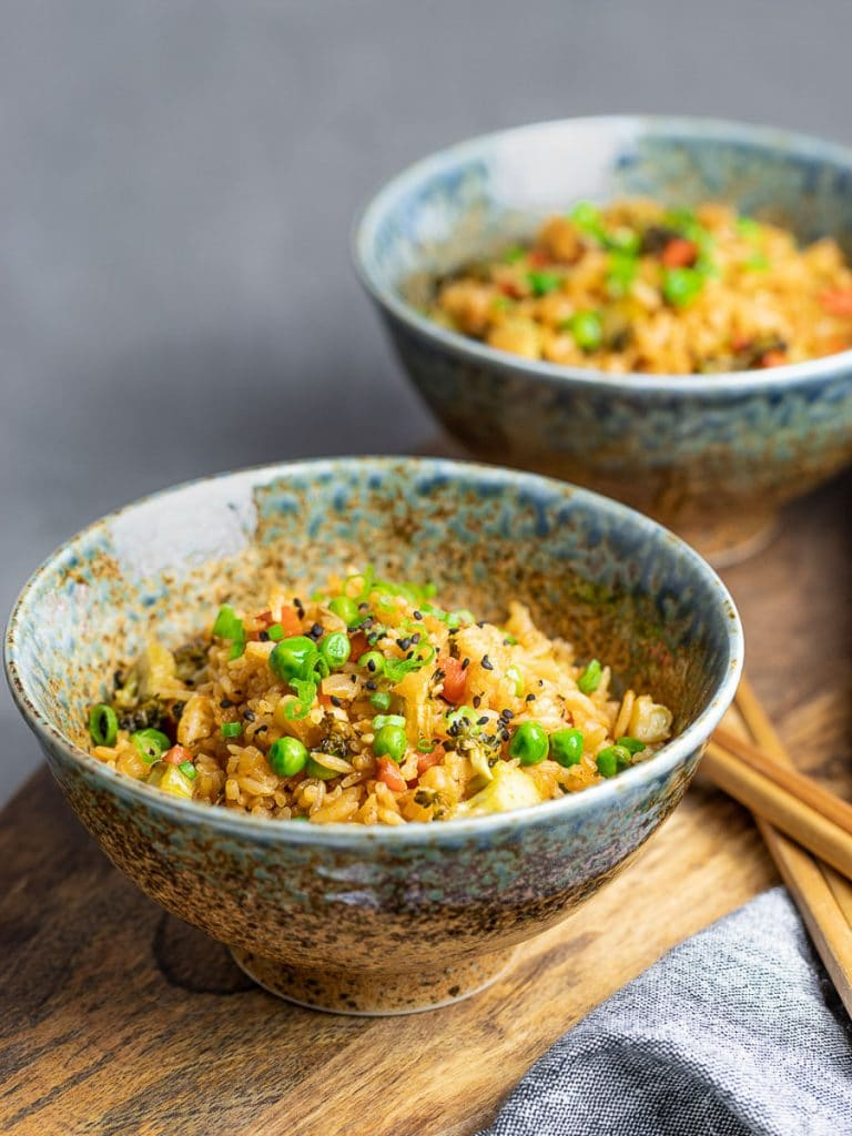ketchup fried rice with green peas and vegetables in two bowls