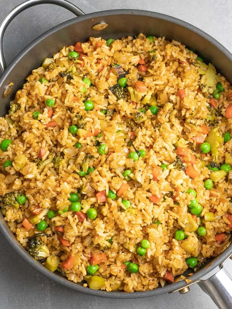 ketchup fried rice with green peas and vegetables in a pan