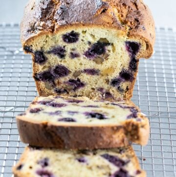 Lemon blueberry bread with a golden brown crunchy crust on a wire rack