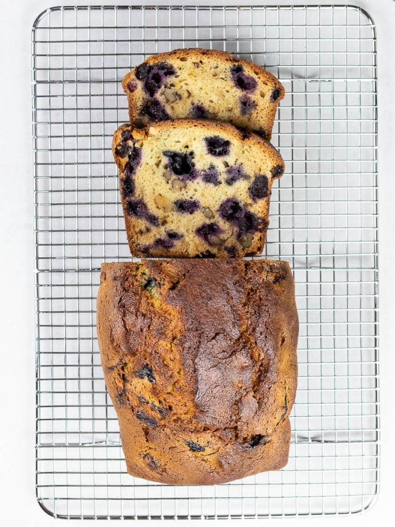 Lemon blueberry bread with a golden brown crust filled with walnuts, blueberries, and lemon zest on a wire rack