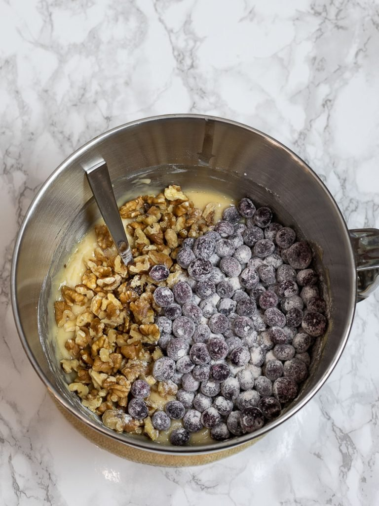 Lemon blueberry bread ingredients including walnuts in a steel mixing bowl