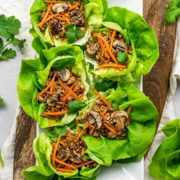 PF Chang's vegetarian lettuce wraps with tofu, mushrooms, carrots, and lettuce on a wooden board