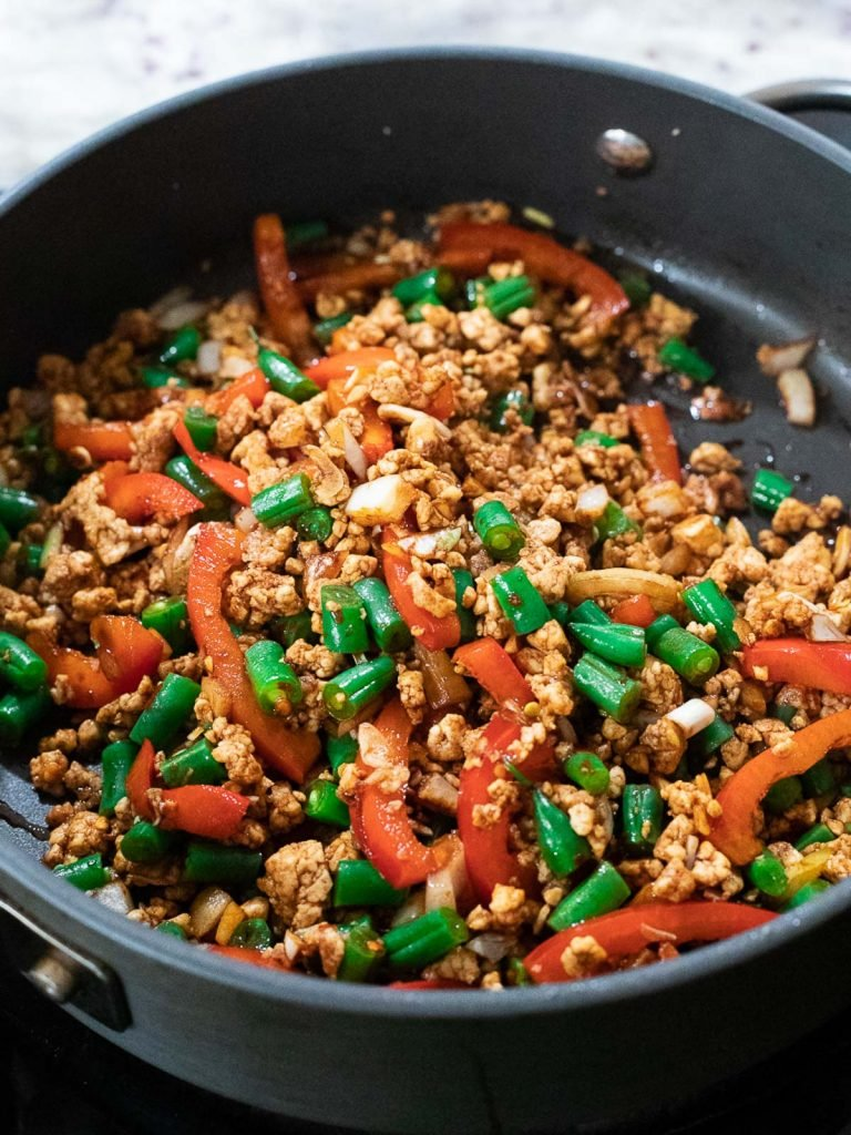 Tofu, green beans, and red peppers in frying pan