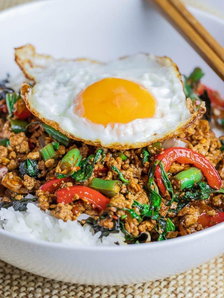 Vegetarian Thai Basil Tofu Stir Fry (Pad Krapow) topped with fried egg in a white bowl with chopsticks