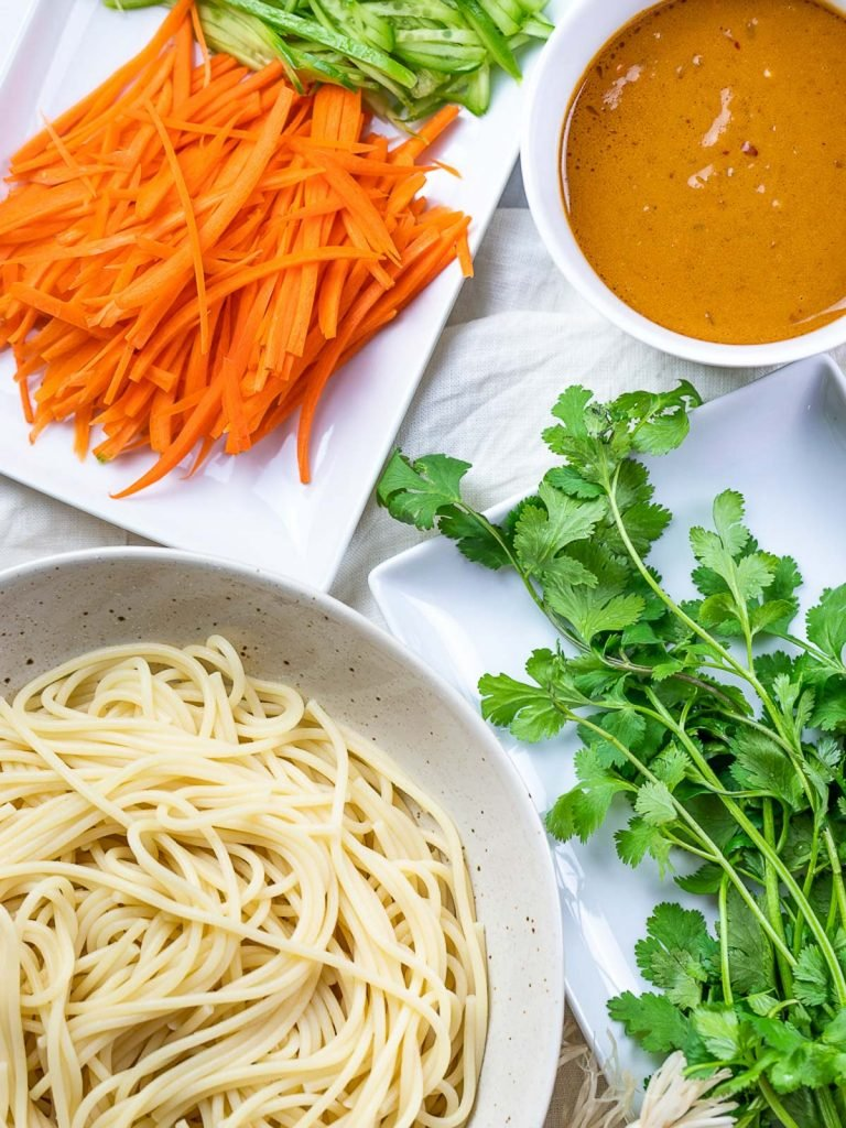 spaghetti noodles, thai peanut sauce, carrots, cilantro