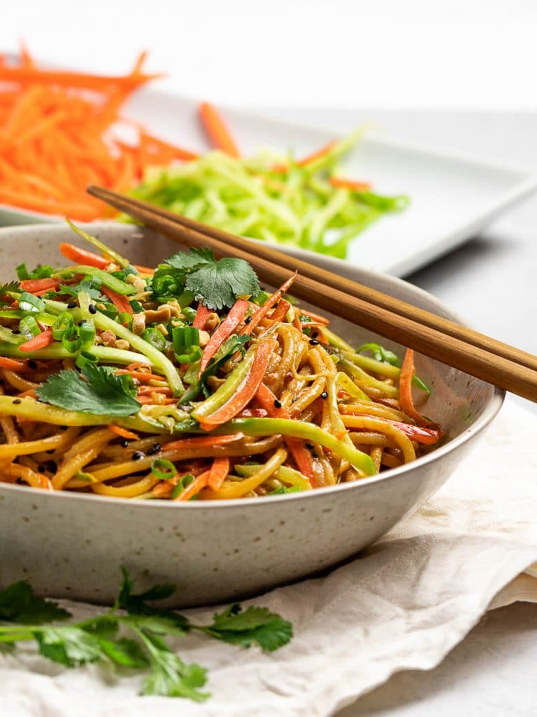 Thai peanut noodles in a bowl with chopsticks