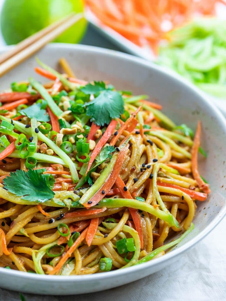 Thai peanut noodles in a bowl with vegetables and herbs