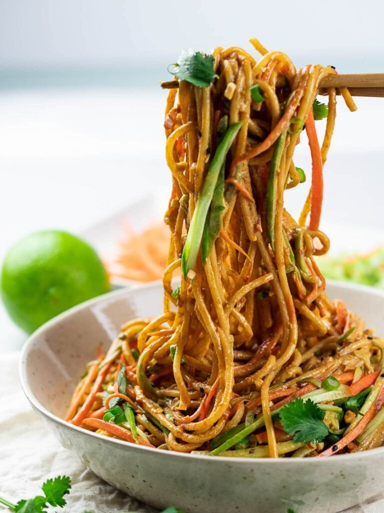 Thai peanut noodles in a bowl held by chopsticks