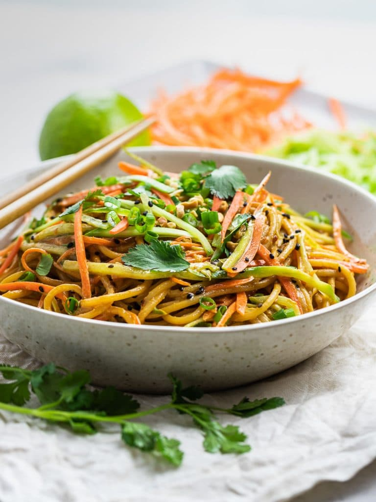Thai peanut noodles in a bowl with herbs and chopsticks