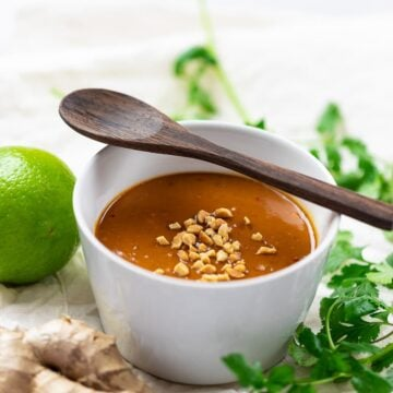 thai peanut sauce in white bowl with wooden spoon