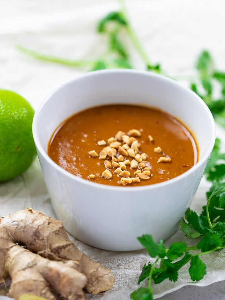 Thai peanut sauce in white bowl with crushed peanuts and ginger and lime