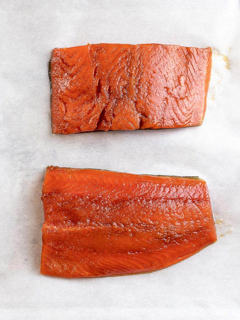 A pair of marinated teriyaki salmon on parchment paper