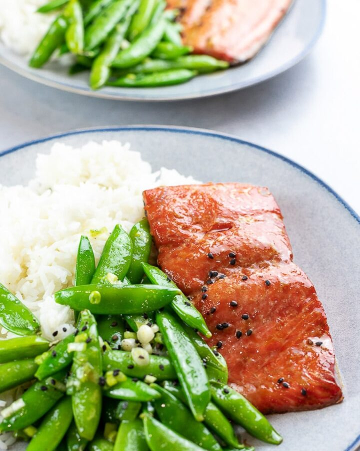 Baked teriyaki salmon with sugar snap peas and rice on a blue plate