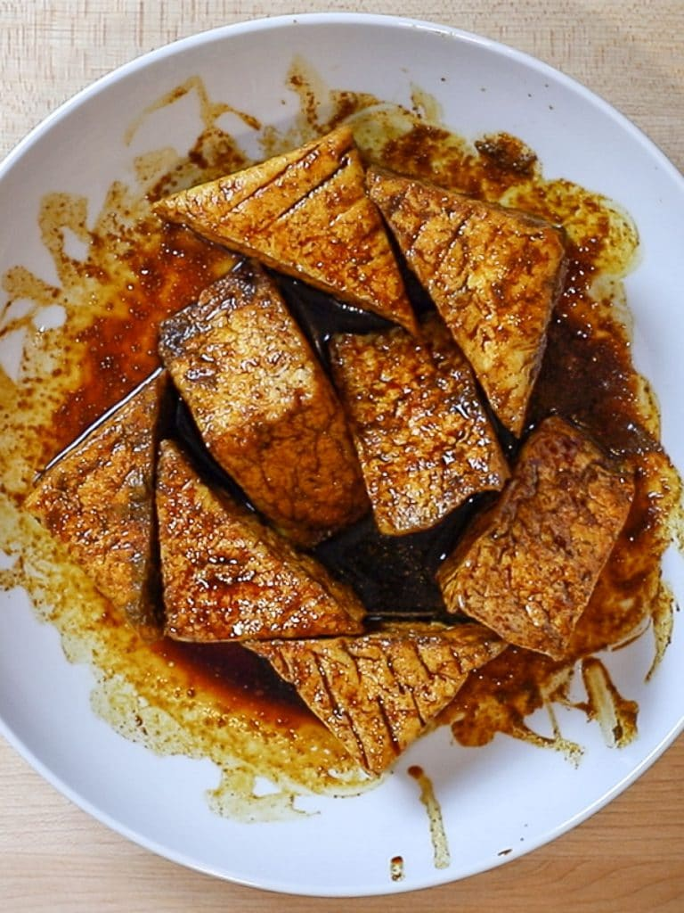 thai tofu satay marinating in a white bowl