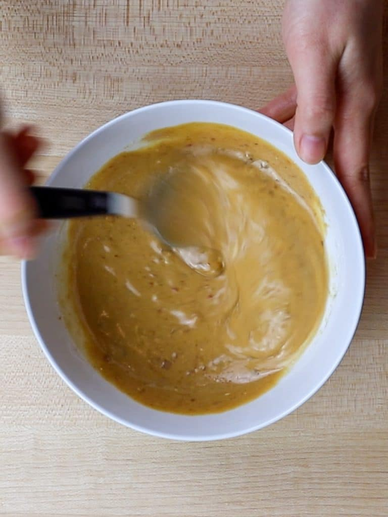 satay peanut sauce with coconut milk mixed in a white bowl