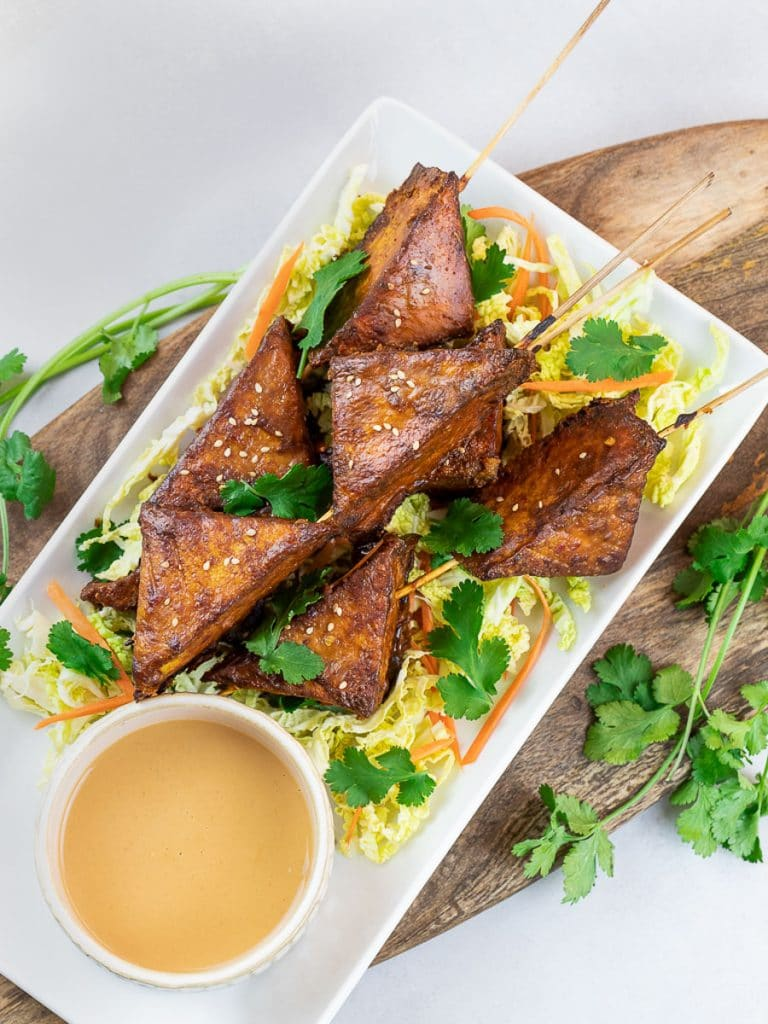 baked thai tofu satay skewers dipped in peanut satay sauce on a white plate with wooden board