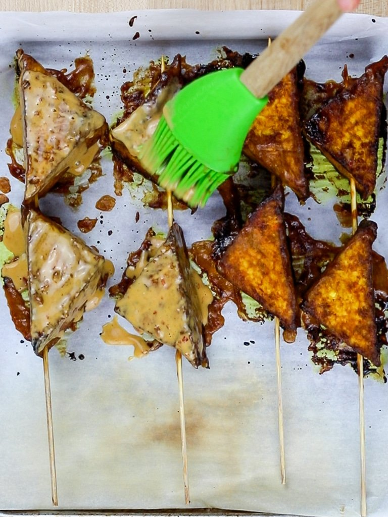 baked thai tofu satay skewers brushed with peanut satay sauce with green silicone brush