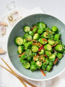 Spicy Asian cucumber salad with herbs and red pepper in a blue bowl next to garlic and chopsticks
