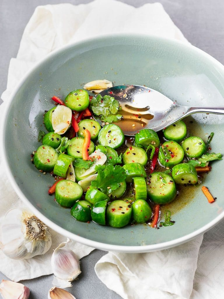 Spicy Asian cucumber salad with herbs and red pepper in a blue bowl with a silver spoon