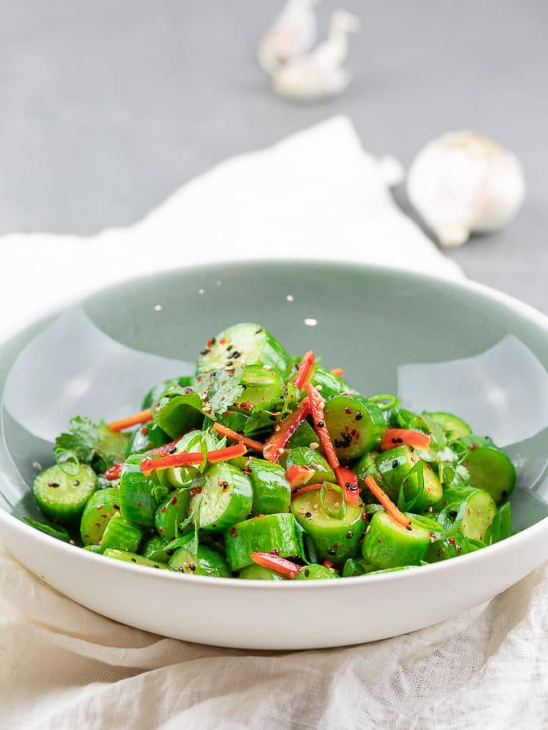 Spicy Asian cucumber salad with herbs and red pepper in a blue bowl