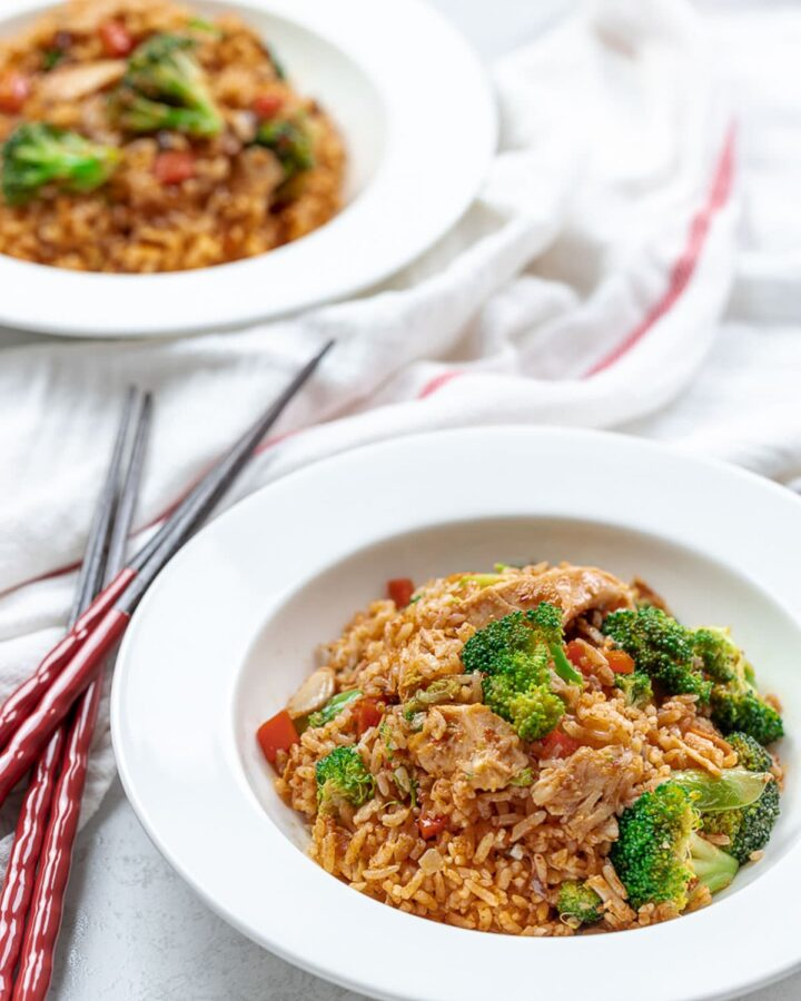 Thai red curry chicken fried rice with broccoli and chicken in white bowls with chopsticks