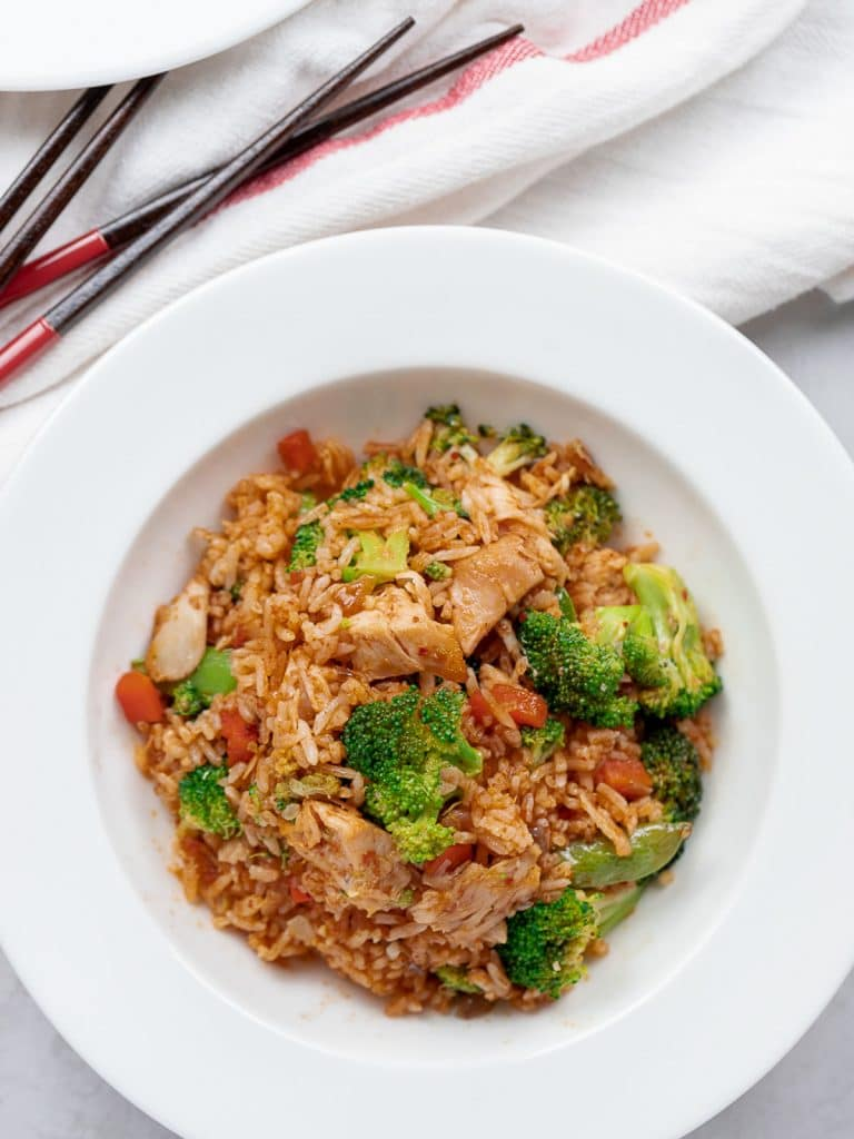 Thai red curry chicken fried rice with broccoli and chicken in a white bowl
